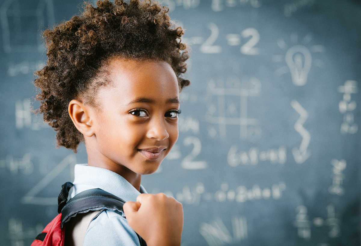 Young girl with backpack in front of blackboard