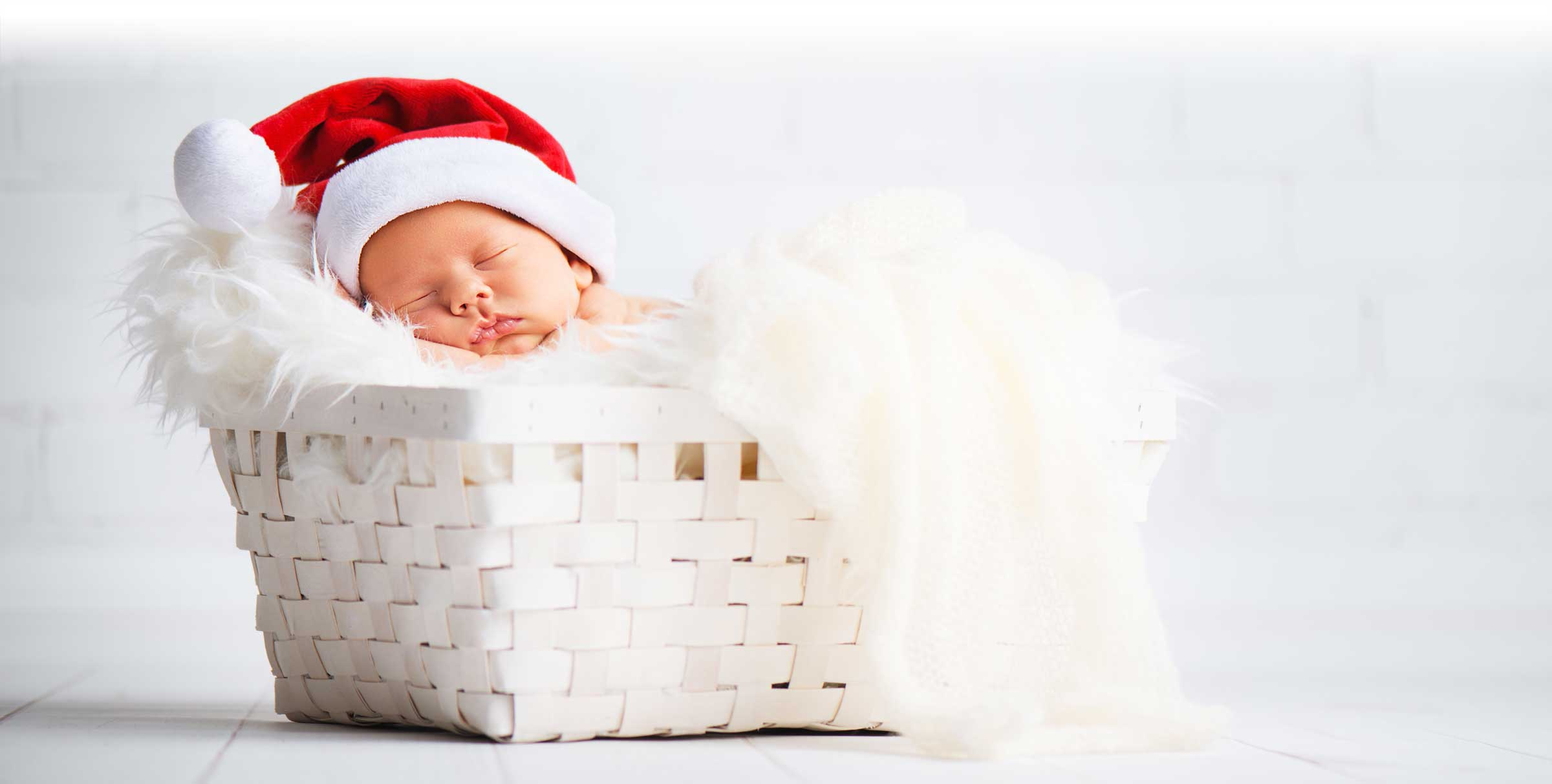 Baby with Santa hat on asleep in basket with blanket