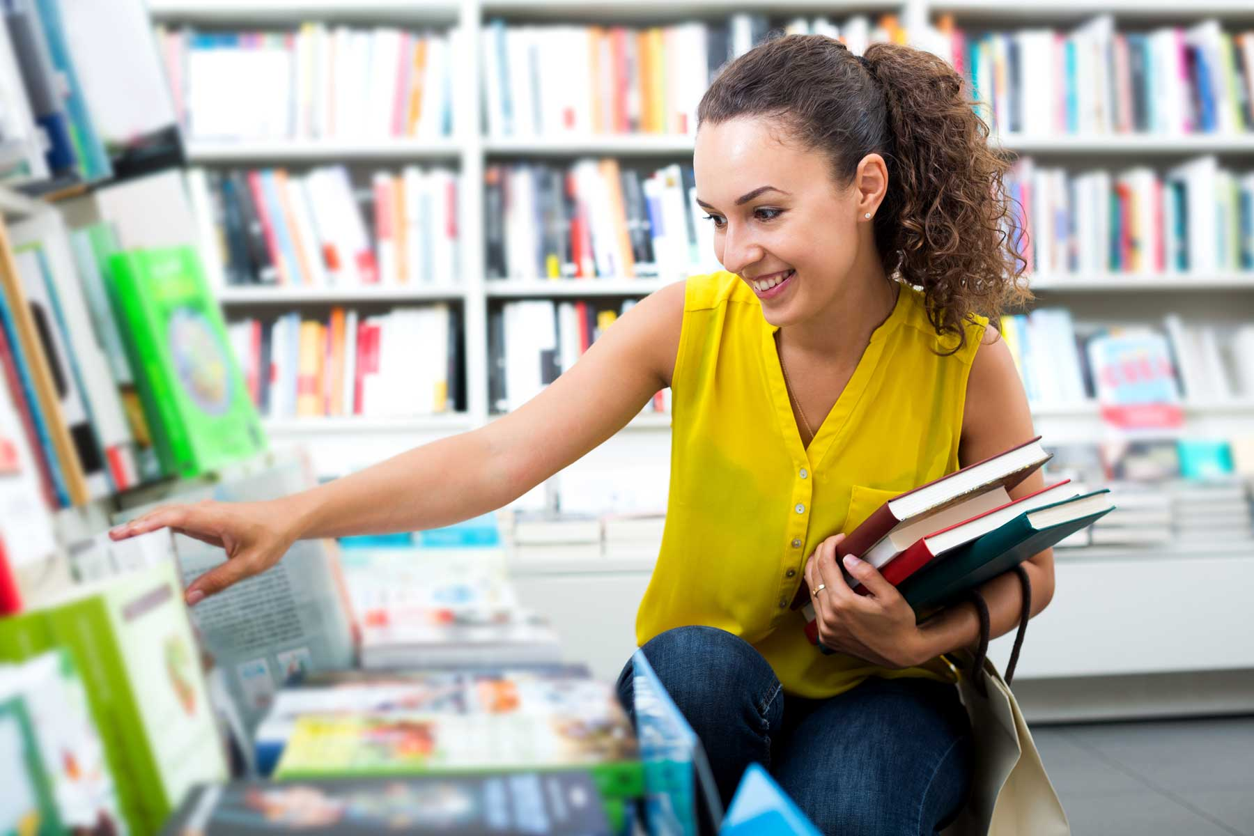 Female college student purchasing books at college bookstore