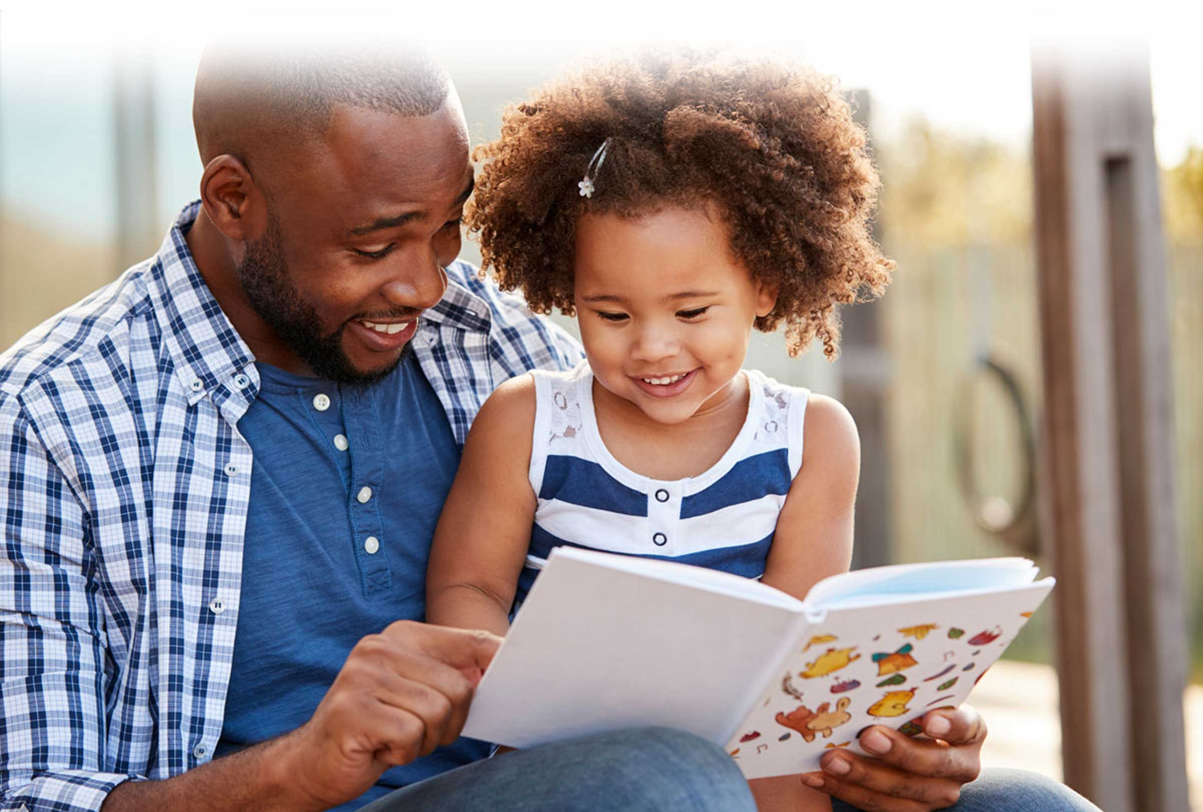 Dad with daughter reading book, smiling, outdoors